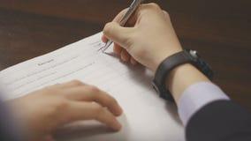 A mão do homem em um terno de negócio assina originais Formulário de enchimento da avaliação vídeos de arquivo