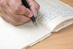 A mão do homem escreve em um papel Fotografia de Stock Royalty Free
