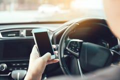 A mão do homem está usando o telefone ao conduzir fotografia de stock