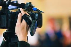 A mão do homem guarda a câmara de vídeo preta digital foto de stock
