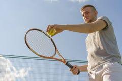 Mão do homem do jogador de tênis que faz um tiro que mantém uma bola e uma raquete contra o céu fotografia de stock royalty free