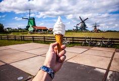 A mão do homem mantém o gelado contra o fundo de moinhos de vento holandeses Fotos de Stock Royalty Free