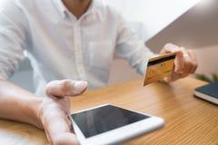 Mão do homem na camisa ocasional que paga com cartão de crédito e que usa o telefone esperto para a compra em linha que faz orden imagens de stock royalty free