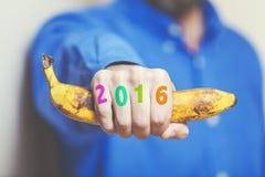 Mão do homem na camisa que guarda a banana Números nos dedos Fotos de Stock