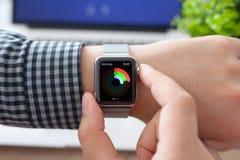 Mão do homem no relógio de Apple com atividade e Macbook Fotografia de Stock