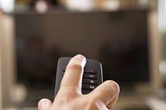 A mão do homem novo com telecontrole muda os canais imagens de stock royalty free