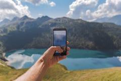 Mão do homem novo que guarda um smartphone e para tomar uma imagem de um panorama surpreendente imagens de stock royalty free