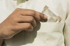 A mão do homem pega uma nota nova da moeda de 500 indianos fora de seu fim do bolso foto de stock royalty free