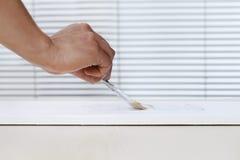 Mão do homem do pintor com pintura da escova de pintura na placa branca, casa imagens de stock royalty free