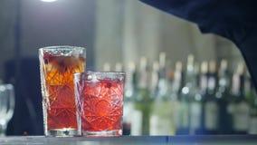 A mão do homem polvilha bagas vermelhas no cocktail de refrescamento com o gelo em fundo unfocused vídeos de arquivo