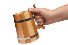 A mão do homem prende a caneca de cerveja de madeira grande Imagens de Stock
