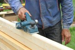 A mão do homem processa uma placa de madeira uma plaina elétrica Imagens de Stock