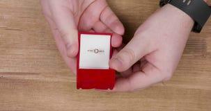 Mão do homem que abre uma caixa vermelha pequena com anel de diamante do acoplamento filme