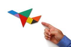 A mão do homem que aponta no plano feito do enigma do tangram Fotos de Stock Royalty Free