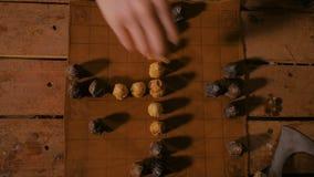 Mão do homem que coloca figuras para o jogo de mesa popular medieval da estratégia - tafl video estoque