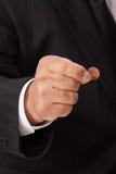 A mão do homem que comprime moeda de um centavo-vertical Fotografia de Stock