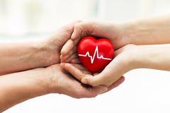 Mão do homem que dá o coração vermelho à mulher Fotos de Stock Royalty Free