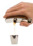 Mão do homem que derrama um líquido marrom no copo do metal Fotos de Stock Royalty Free