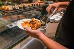 Mão do homem que escolhe o sushi, lagosta imagens de stock royalty free