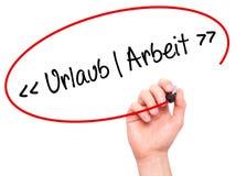 Mão do homem que escreve Uralaub Arbeit (férias - trabalho no alemão) com foto de stock