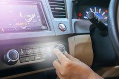 Mão do homem que gira sobre o sistema de condicionamento de ar do carro, botão no painel no carro foto de stock royalty free