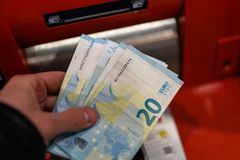 Mão do homem que guarda euro- cédulas na máquina do ATM no banco no centro de compra fotografia de stock royalty free