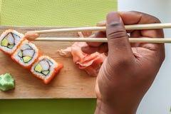 A mão do homem que guarda hashis e que come rolos de sushi de Califórnia em uma placa de madeira imagem de stock