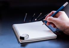 Mão do homem que guarda o lápis e que escreve o bloco de notas Fotos de Stock Royalty Free