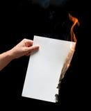 Mão do homem que guarda o papel queimado branco Fotos de Stock