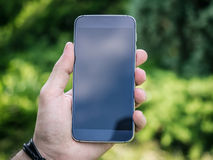 A mão do homem que guarda o smartphone móvel Imagens de Stock