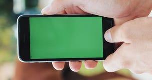 A mão do homem que guarda o smartphone no Internet de conversa dos apps do fundo do borrão do chromakey do modelo da tela do verd filme