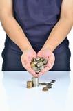 Mão do homem que guarda a pilha das moedas Foto de Stock