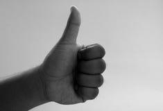 Mão do homem que guarda um polegar imagens de stock