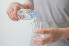 Mão do homem que guarda uma garrafa da água de derramamento da água em um vidro imagem de stock