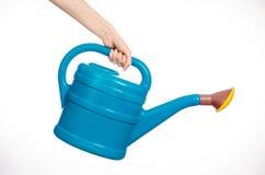 A mão do homem que guarda uma grande lata molhando plástica azul no branco Imagens de Stock
