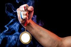 Mão do homem que guarda uma medalha de ouro foto de stock royalty free