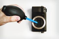 A mão do homem que guarda uma pera para a poeira de limpeza da câmera foto de stock