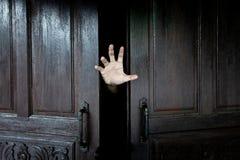 A mão do homem que guarda a vara da porta de madeira do interior da obscuridade foto de stock royalty free