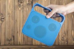 A mão do homem que leva o orador acessível azul no fundo de madeira Imagens de Stock Royalty Free