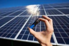 A mão do homem que mantém o detalhe minúsculo para a instalação da bateria solar imagens de stock royalty free