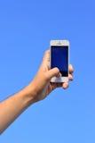 A mão do homem que mantém um telefone contra o céu Fotografia de Stock Royalty Free