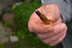 Mão do homem que mostra 7 bala da munição de 62 calibres Fotografia de Stock Royalty Free