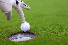 A mão do homem que põe uma bola de golfe no furo sobre Fotografia de Stock Royalty Free