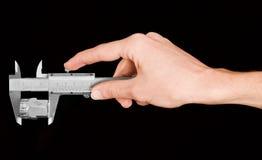 Mão do homem que prende um compasso de calibre durante a medição Fotografia de Stock Royalty Free