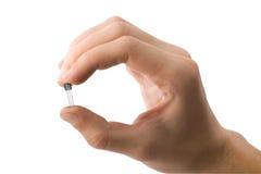 A mão do homem que prende um transistor isolou-se Imagens de Stock