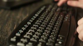 Mão do homem que trabalha no computador que datilografa no teclado filme