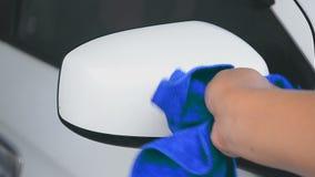 Mão do homem que usa a micro tela azul da fibra para limpar o carro filme