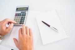 Mão do homem que usa uma calculadora Fotografia de Stock