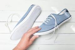 A mão do homem seleciona as sapatilhas de calças de ganga em um fundo de madeira branco imagem de stock royalty free