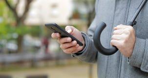Mão do homem usando um telefone esperto sob a chuva video estoque